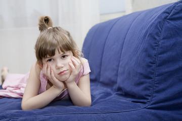 cute sceptical  little girl lying on sofa