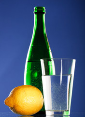 green bottle with lemon and glass
