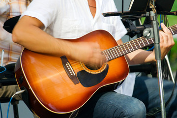 man is playing on acoustic guitar