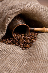 Wall Murals Coffee beans Cezve with freshly roasted coffee beans on sackcloth