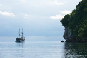 Yacht sailing next to rocky island