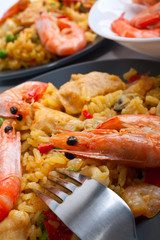 Spanish paella on dark plates with king shrimps