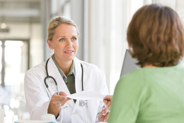 Attractive young caring doctor talking to patient