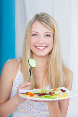 Pretty girl holding salad on fork and plate