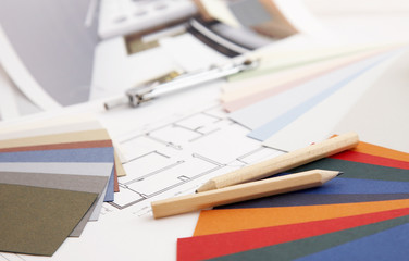 designer's desk with tools, color sample and blueprint