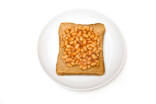 Plate of baked beans on toast, isolated on a white background.