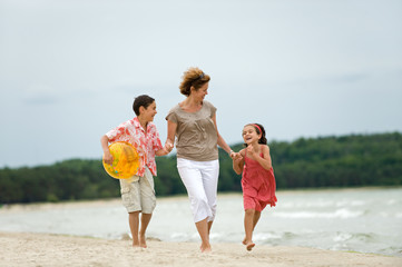 Happy mother and kids walking on the beach