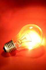 Light bulb glowing on red background
