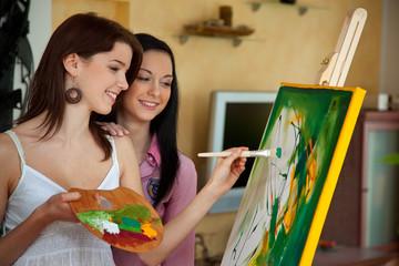 Junges Mädchen malt an einer Staffelei