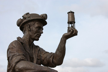 A Statue of a Coal Miner Looking at his Miner's Lamp.