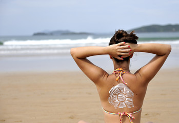 Woman taking sun with suncream draw on her back