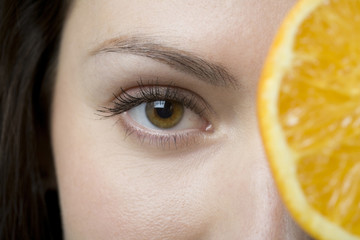 Close up of woman holding sliced orange