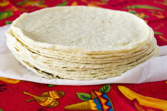 Stack of fresh corn tortillas on red tablecloth.