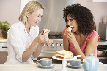 Female Friends Enjoying Tea And Cake At Home