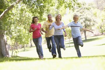 Family Running Through A Park