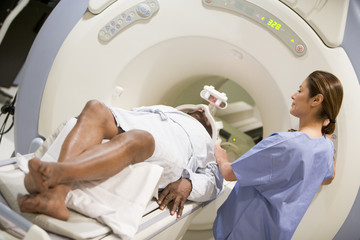 Nurse With Patient As They Prepare For A CAT Scan