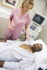 Nurse Checking On Patient Lying On Hospital Bed
