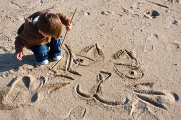 Little Boy Drawing Cat in the Sand
