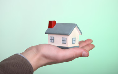 Small house in hand on green background