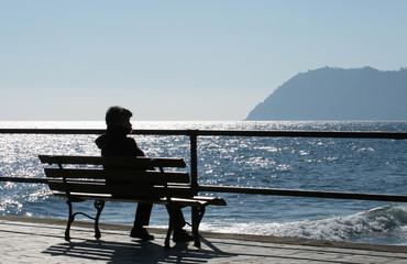 donna anziana seduta di fronte al mare