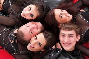 Five teenagers smiling close up.