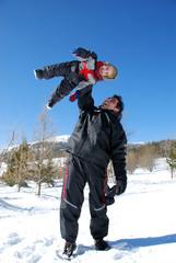Père qui joue avec son enfant à la neige