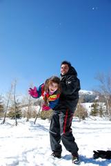 papa qui joue avec sa fille au sport d'hiver.