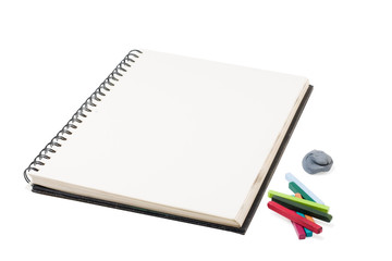 sketchbook and pastel crayons on a white background