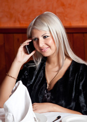 Charming blond girl talking on the phone at the table in a resta