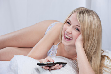 Smiling woman on bed holding remote controller