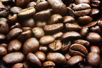 Heap of brown roasted coffee beans close up photo as background