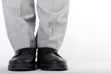 Man in black shoes and grey trousers
