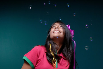 soap bubbles blowing downwards on the head of girl