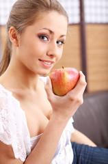 Young beautiful woman eating green apple