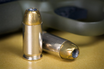 .45 Caliber Hollow Point Pistol Bullets Standing Near Handgun