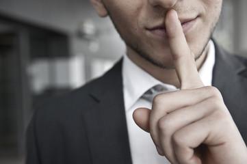 Fototapeta mann mit anzug legt finger auf lippen obraz