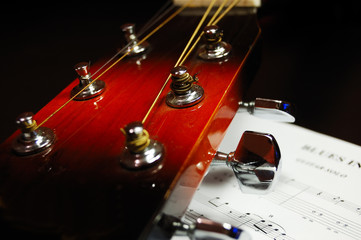 Guitar headstock and tuning peg against a blues sheet music