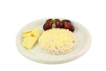 chesse, grapes and a rice cake on a white plate