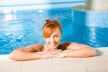 Young happy woman in pool