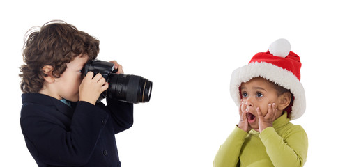Little photographer making a picture of a baby with Santa Claus