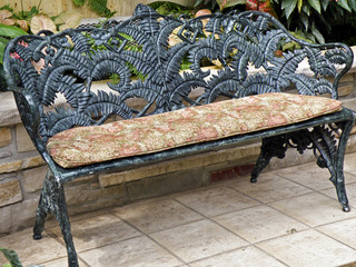 black ornate bench on tiled patio