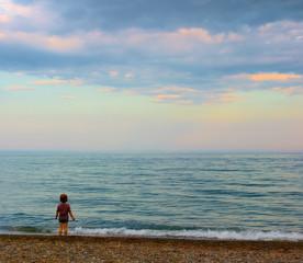 A girl watching beautiful sunset from seashore