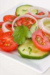 Tomaten-Gurkensalat auf einem weißen Teller