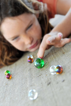 Young girl playing marbles