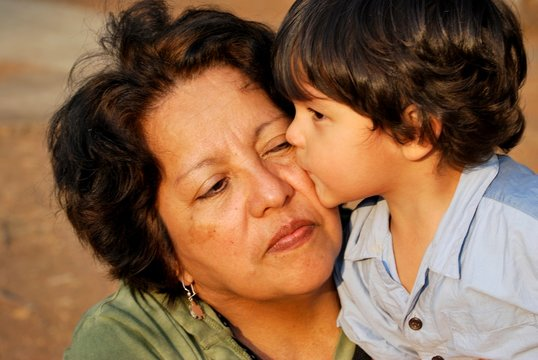 Adorable grandson gives a kiss to his grandmother