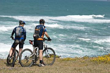 Two cyclists on sea beach