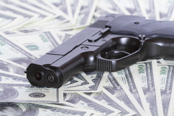 Automatic pistol on background with money