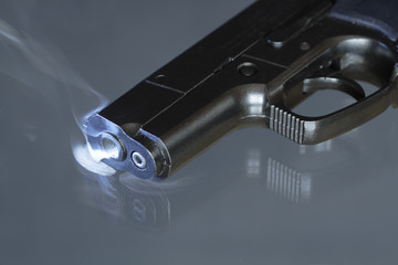Automatic pistol after shooting on dark background