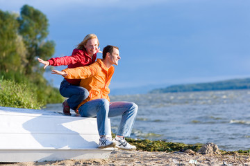Young love Couple sit on boat on coast of river
