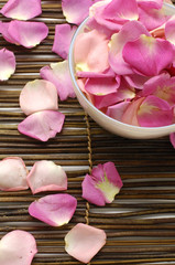 Photo sur Aluminium Spa Bowl of rose petals on bamboo spa mats.
